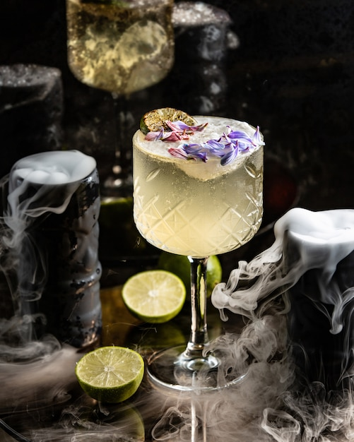 Lime cocktail garnished with lime and flower petals in long stem glass Free Photo