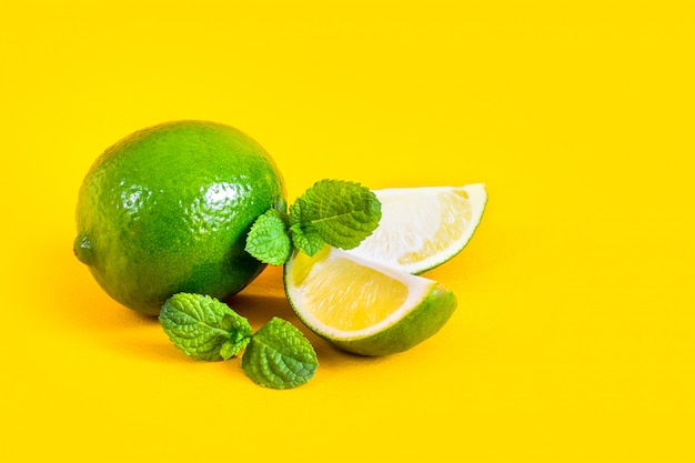 Lime slices and green mint leaves on a yellow Premium Photo