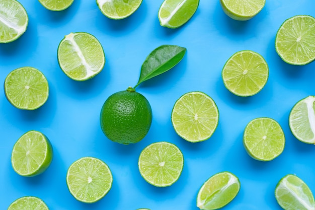 Limes with leaf on blue. top view Premium Photo