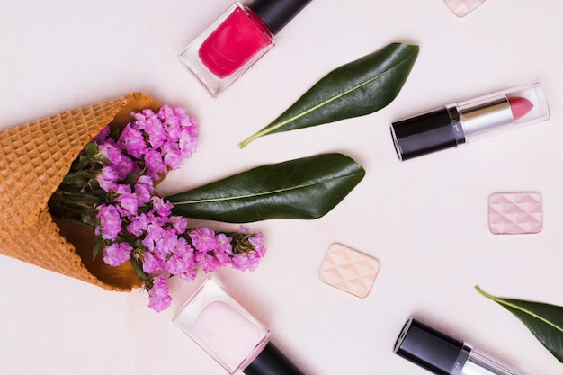 Limonium and leaf inside the waffle cone; nail polish bottle; lipstick and eye shadows on pink background Free Photo
