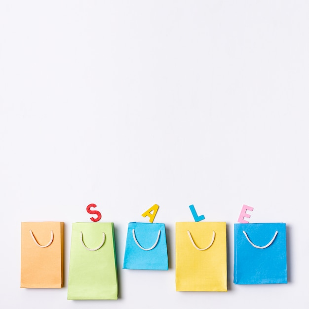 Line of coloured paper bags with sale text concept Free Photo