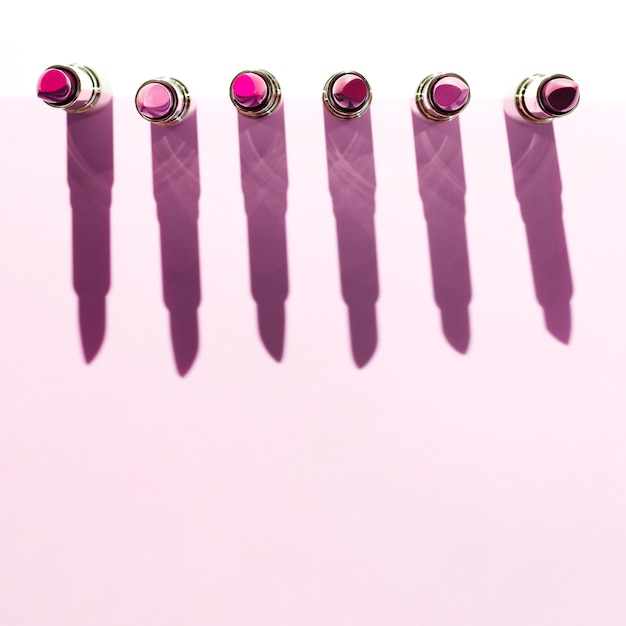 Line of metallic lipsticks on pink background Free Photo