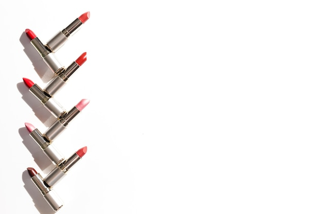Line of metallic lipsticks on white background Free Photo