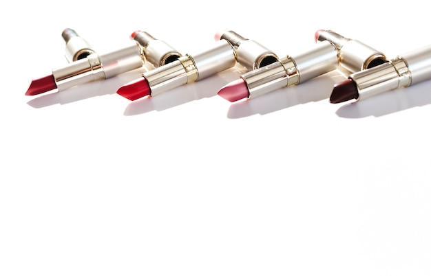 Line of metallic lipsticks on white background Free Photo