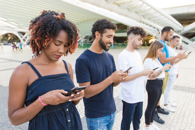 Line of mix raced people texting messages on smartphones Free Photo