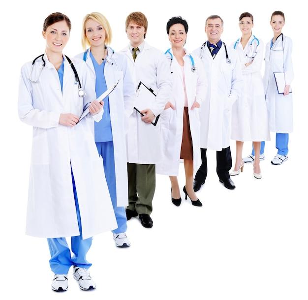 Линия группы счастливых врачей в больничных халатах, изолированные на белом Бесплатные Фотографии