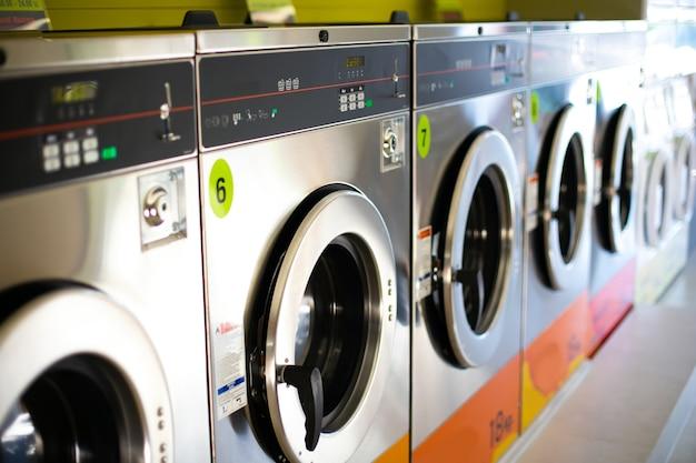 公共のコインランドリーにある工業用洗濯機のライン。 Premium写真
