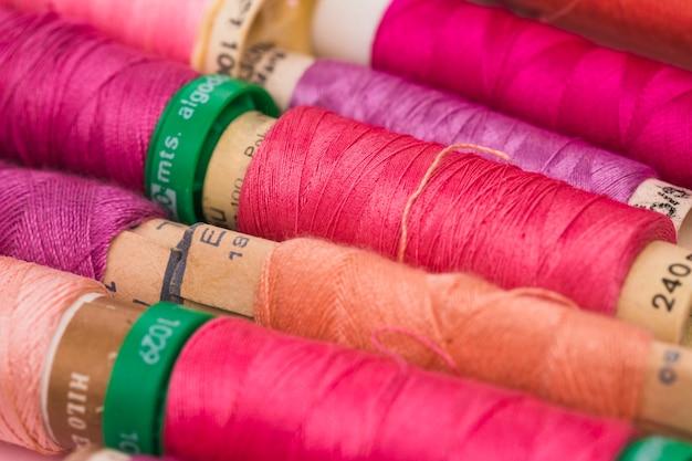 Line of reels of warm colors yarn Free Photo