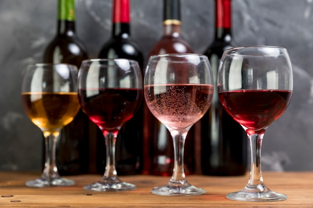 Line of wine bottles and wineglasses Free Photo