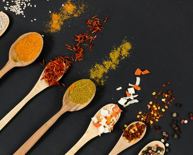 Line of wooden spoons full of spices Free Photo