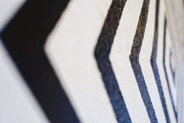 Lines like black arrows on white background painted on a wall indicating direction. Premium Photo
