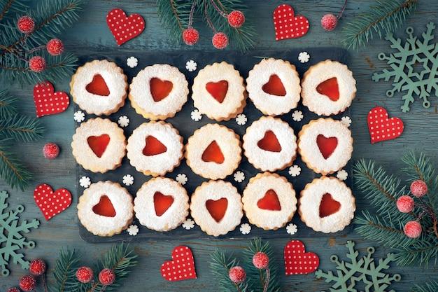 Вид сверху традиционного рождественского печенья linzer с красным вареньем на деревенском дереве, украшенном ягодами Premium Фотографии