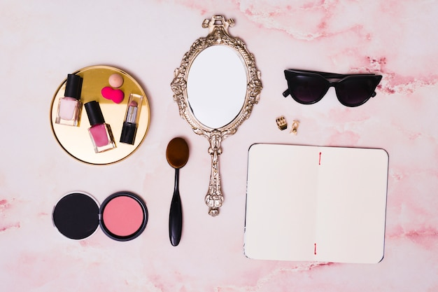 Lipstick; nail polish bottles; compact face powder; makeup brush; hand mirror; clutcher and open blank diary on pink backdrop Free Photo