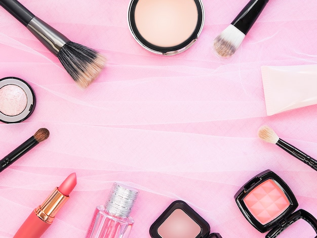 Lipstick, tools, eyeliner, blush, perfume, eye shadow and powder cosmetic in pink theme make up on frame for promotion. Premium Photo