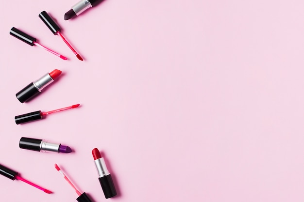 Lipsticks and lip glosses scattered on pink background Free Photo