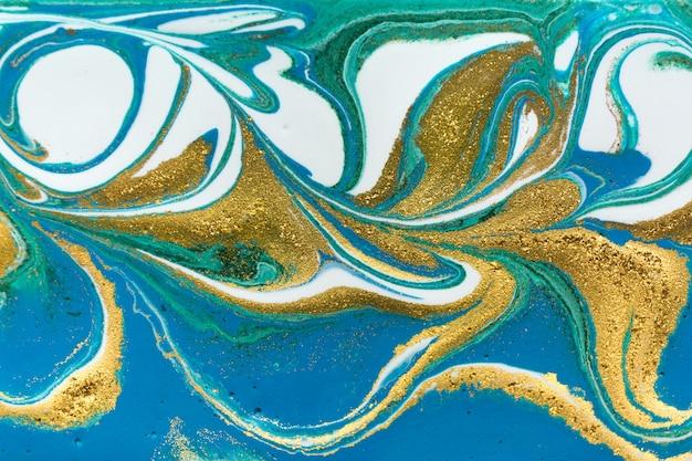 Liquid uneven blue and green golden glitter and glare of light Premium Photo