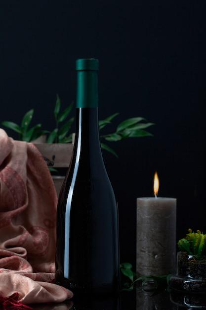 Бутылка ликера со свечой, шарфом и растением в горшке Бесплатные Фотографии