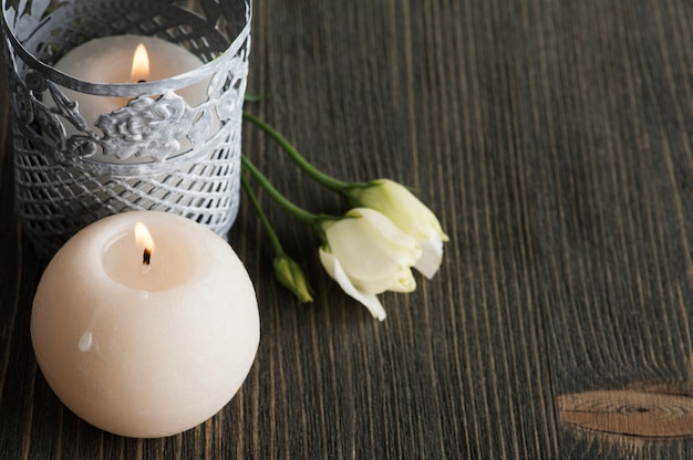 Lit candles and white flowers on dark rustic table Premium Photo