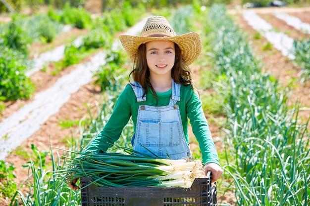 Litte kid farmer girl in onion harvest orchard Premium Photo