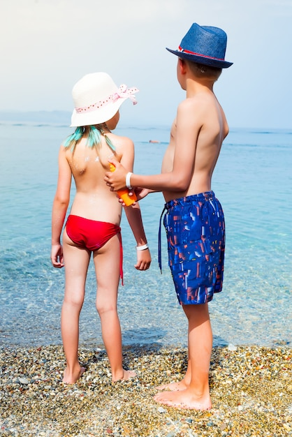 Little adorable boy with hat applying sun cream to his sister on the sea beach. Premium Photo