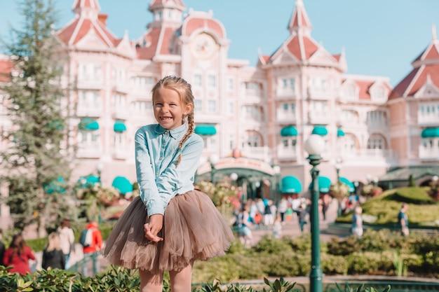 Little adorable girl in cinderella dress at fairy-tale disneyland park Premium Photo