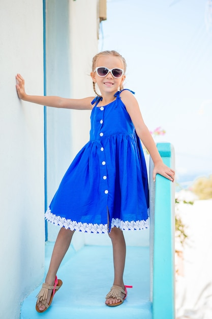 Little adorable girl in dress outdoors in old streets an mykonos. Premium Photo