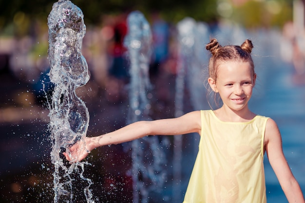Little adorable girl have fun in street fountain at hot sunny day Premium Photo
