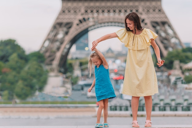 Little adorable girl and her young mom in paris near eiffel tower during summer vacation Premium Photo