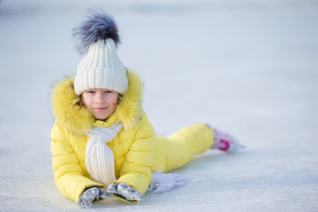 Little adorable girl lying on ice with skates after fall Premium Photo