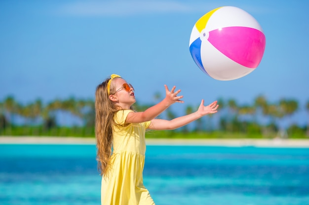 Little adorable girl playing on beach with ball Premium Photo