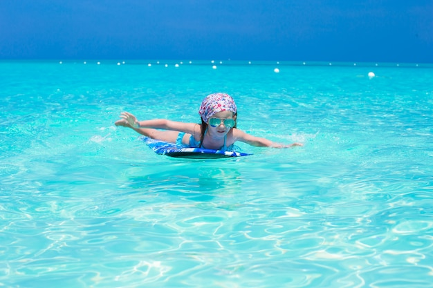 Little adorable girl on a surfboard in the turquoise sea Premium Photo