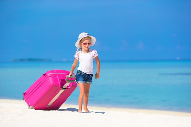 Little adorable girl with big suitcase on tropical white beach Premium Photo