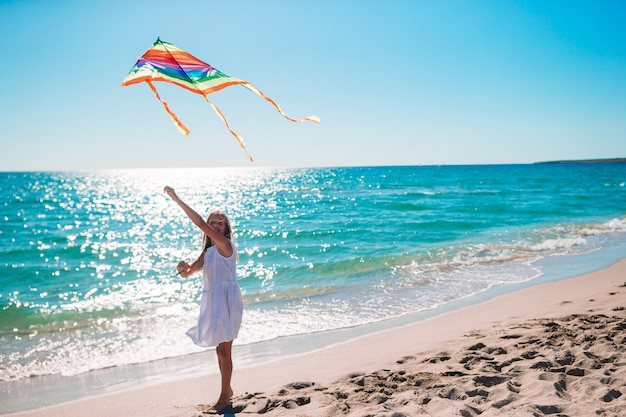 Little adorable girl with flying kite Premium Photo