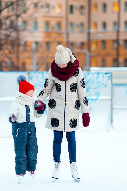 Little adorable girl with mother skating on ice-rink with mother Premium Photo