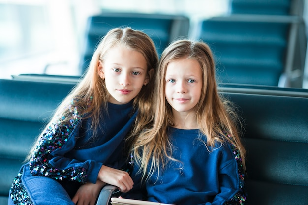 Little adorable girls in airport waiting for boarding near big window Premium Photo