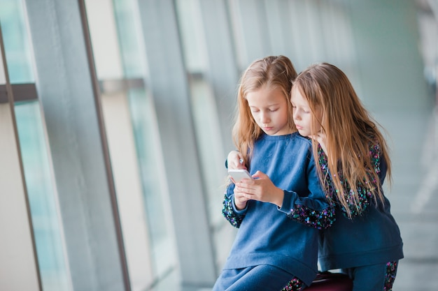 Little adorable girls in airport waiting for boarding and playing with laptop Premium Photo
