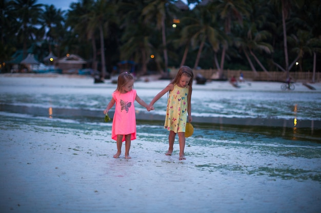 Little adorable girls in exotic resort in nice dress in the evening Premium Photo