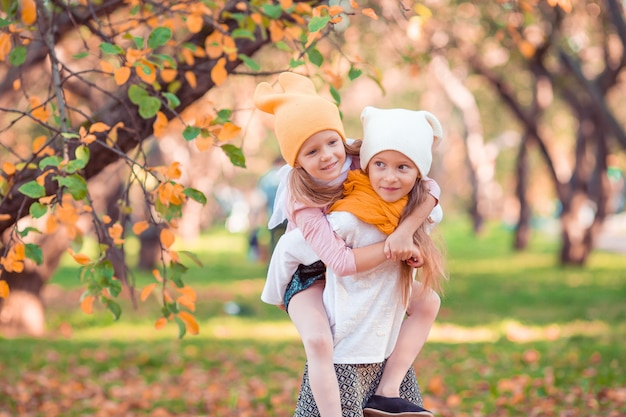 Little adorable girls outdoors at warm sunny autumn day Premium Photo
