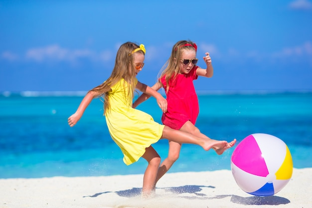 Little adorable girls playing on beach with air ball Premium Photo