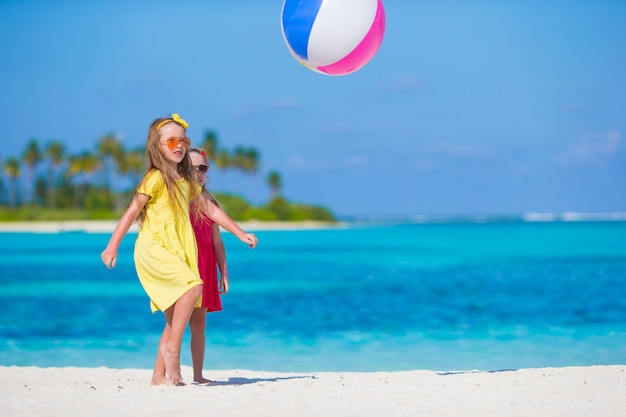 Little adorable girls playing on beach with ball Premium Photo