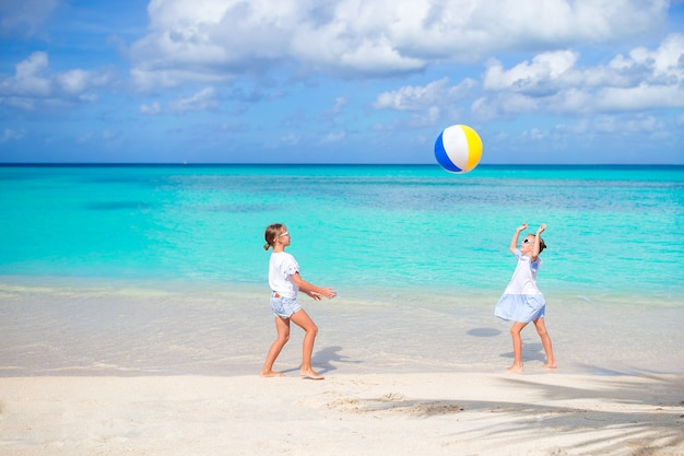 Little adorable girls playing with ball on the beach Premium Photo