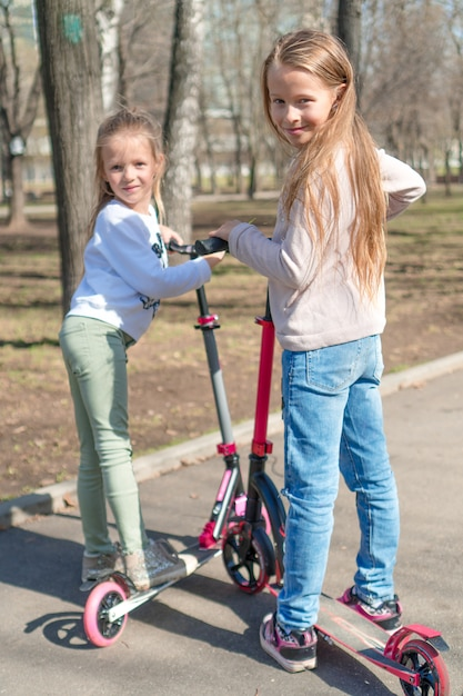 Little adorable girls riding on scooters in park outdoors Premium Photo
