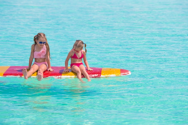Little adorable girls on a surfboard in the turquoise sea Premium Photo