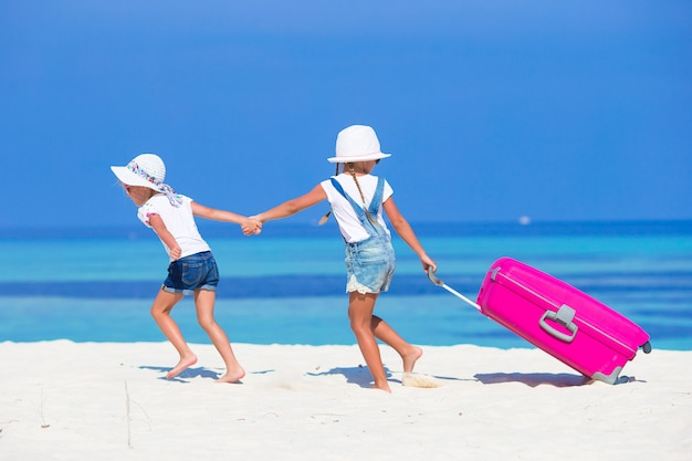 Little adorable girls with big suitcase on tropical white beach during summer vacation Premium Photo