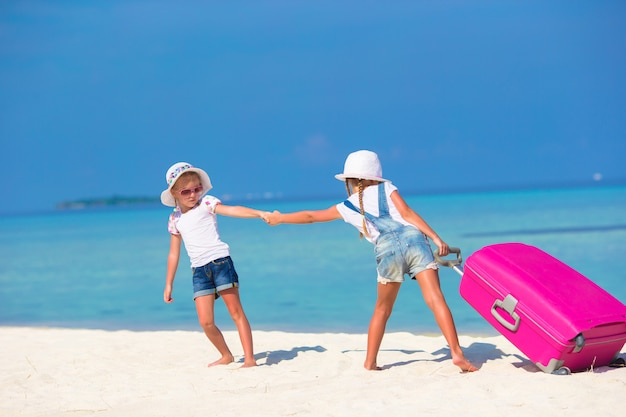 Little adorable girls with big suitcase on tropical white beach Premium Photo