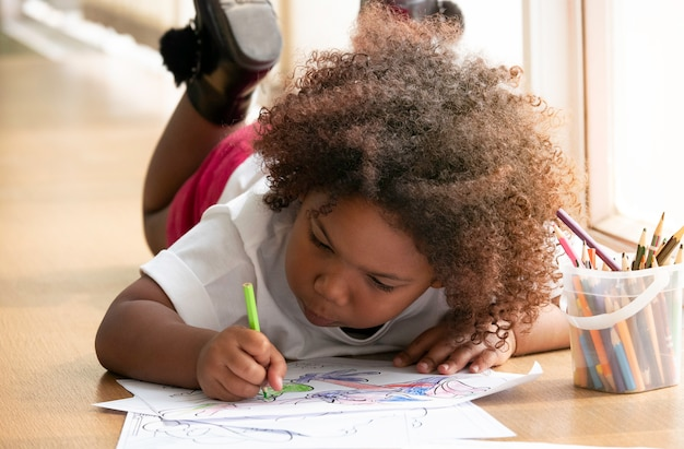 Little african girl painting and drawing with happiness. Premium Photo