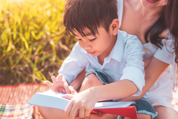 Little asian boy and his mother reading tale story books at meadow field. mother and son learning together. Premium Photo