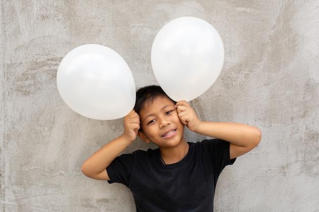 Little asian boy holding white balloons over grey concrete background. Premium Photo