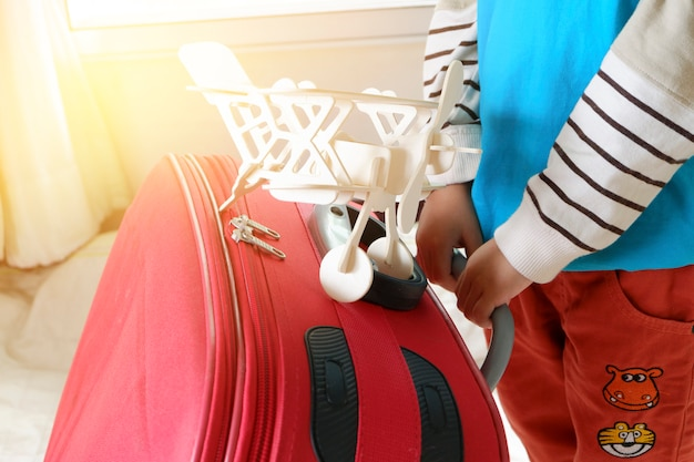 Little asian boy ready to travel with suitcases and his toy airplane, travel and adventure concept Free Photo