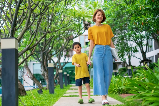 A little asian boy with his mother walks in garden Premium Photo
